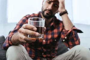 A man holds a glass and wonders if he should enroll in an alcohol addiction treatment program