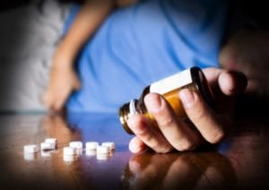 A man lies on the floor, grasping a bottle of pills, and wondering about opioid addiction facts